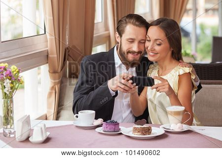 Cute boyfriend and girlfriend are using telephone in cafe