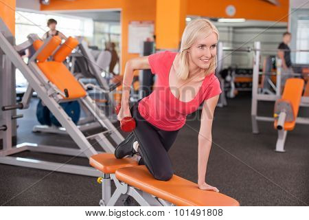 Cheerful young woman is training with weights in fitness center