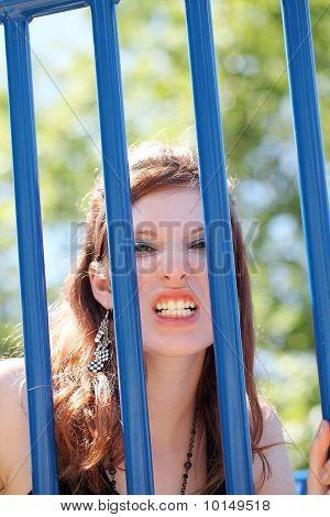 Young Caucasian Teen Girl Snarling Through Bars