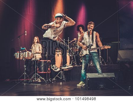 Multiracial music band performing on a stage