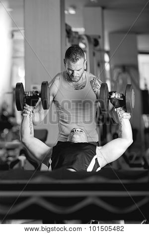 Personal Trainer Helping A Young Man With Dumbbell.