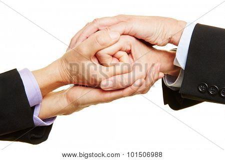 Two businesspeople folding hands together as a spiral
