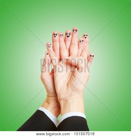 Many fingers with funny smileys talking as a team to each other