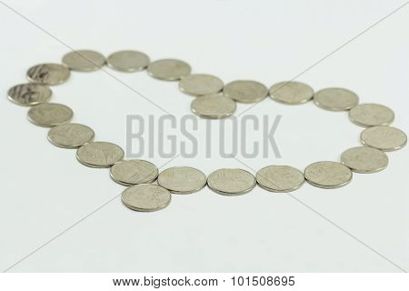 Coins In The Shape Of A Heart Isolated On White
