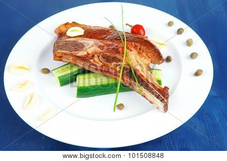 hot red beef meat steak on white plate with capers and tomatoes on blue wooden table