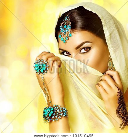 Arabian woman portrait. Arab girl with oriental jewellery and make-up hiding her face behind a veil and smiling. Brunette Hindu model girl with Indian jewels. Traditions