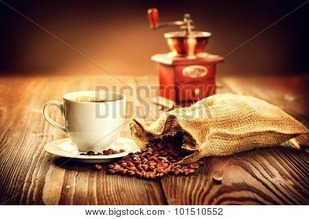 Cup of aromatic coffee on saucer with burlap sack full of roasted coffee beans and coffee grinder on wooden table. Cup of warm coffee with bag with coffee grain over vintage wooden background