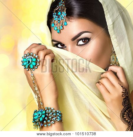 Brunette Indian woman portrait. Indian girl in sari with mehndi tatoo and make-up hiding her face behind a veil, smiling and looking in camera. Hindu model girl. Marriage Traditions