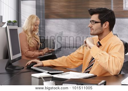 Businessman sitting at desk in office, working with computer.