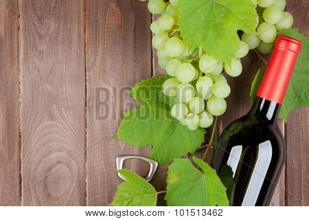 Bunch of grapes, red wine bottle and corkscrew on wooden table background with copy space