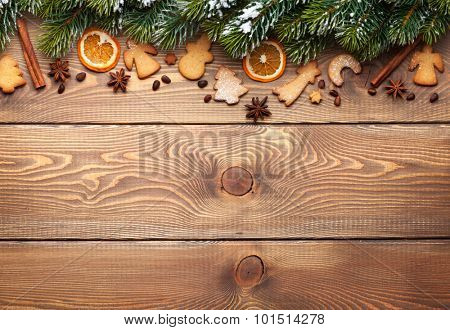 Christmas wooden background with snow fir tree, spices, gingerbread cookies and copy space
