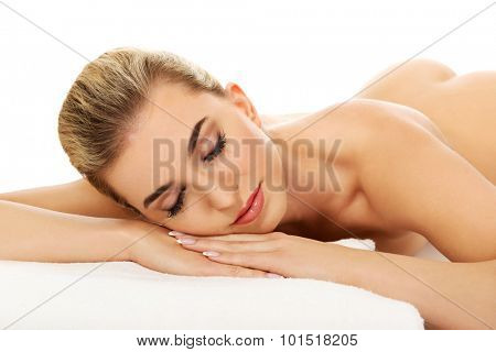 Young woman lying on massage table, isolated on white.