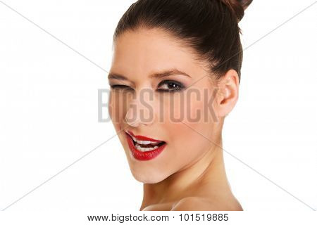Attractive topless woman with dark make up blinks eye.