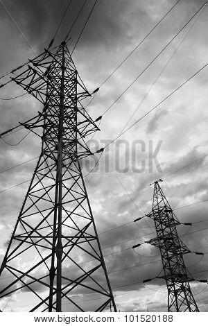 High voltage electricity pylons against rainy cloud.