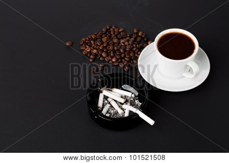 White cup of coffee with ashtray and beans