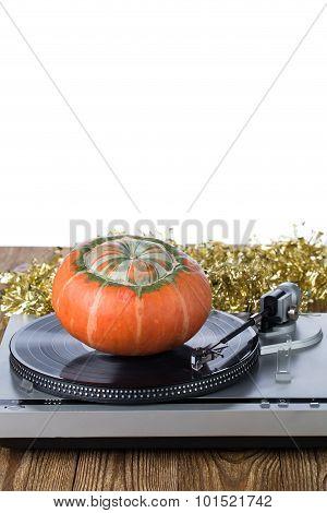 Grey vintage record player and orange pumpkin