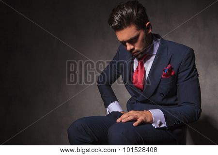 Thoughtful young man sitting on a chair while looking down.