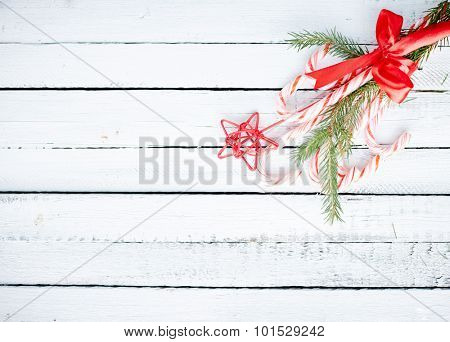 Christmas bouquet made up of candy canes, red star and conifer branches over wooden background