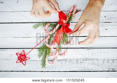 Human hands binding Christmas bouquet made up of candy canes, red star and conifer