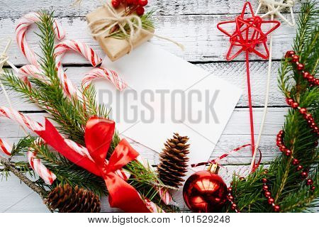 Christmas composition made up of conifer branches, cones, decorative bubble, stars, beads, candy canes and small giftbox on wooden background