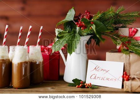 Vase with guelder leaves and berries, bottles with hot chocolate topped with whipped cream and several giftboxes