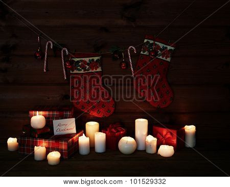 Christmas socks, sugar canes, toy bubbles, burning candles and giftboxes on wooden background