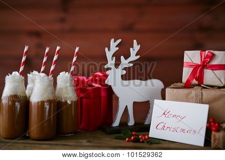 Toy deer, bottles with hot chocolate topped with whipped cream and giftboxes
