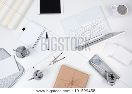 High angle shot of a business desk mock up. A neat white desk with objects either white or silver.