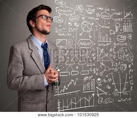 Attractive young man looking at stock market graphs and symbols