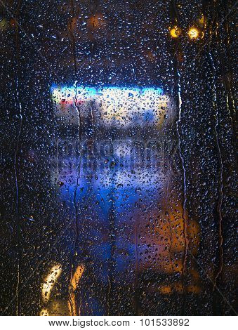 Raindrops on the window with urban night lights - vertical