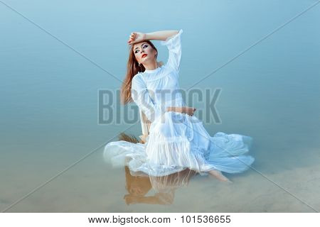 Girl On Chair Sits In The Middle Lake.