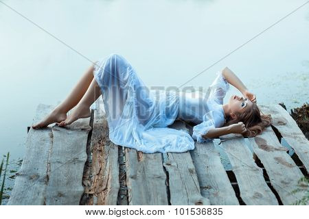 Beautiful  Tender Woman Lying On The Jetty And Bored.