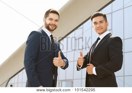 Smiling business partners giving a thumb's up