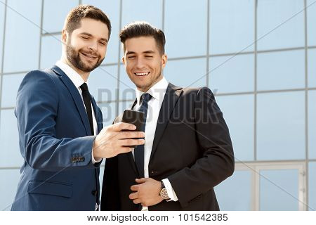 Two colleagues discussing something on a cellphone