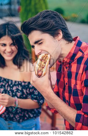 Young man eating hot dog and woman laughing in background