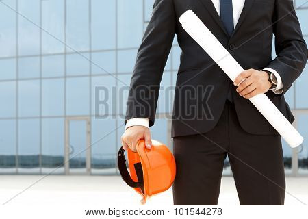 Successful architect with hardhat and plueprints
