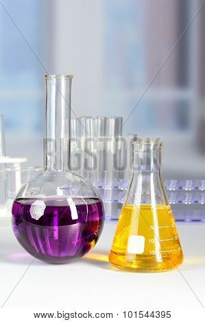 Laboratory flask and beaker with colored liquids over white table