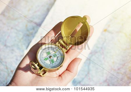 Compass in the hand against a map