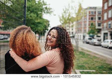 Young Woman Walking With Her Friend Along City Street