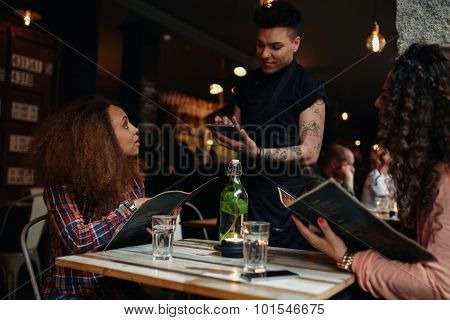 Young Women Giving Order To A Waiter At Cafe