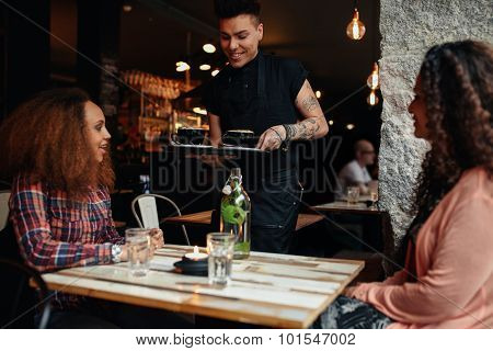 Waiter Serving Coffee To Customers At Cafe