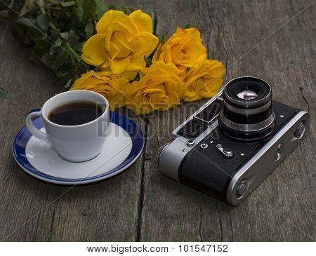 The Ancient Film Camera, Bouquet And Coffee On An Old Wooden Table, A Still Life