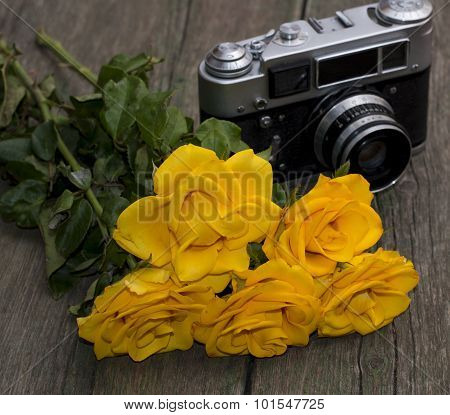 Bouquet Of Beautiful Yellow Roses And The Old Camera On A Wooden Background