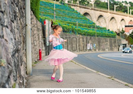 Outdoor portrait of a cute little girl of 7 years old, walking to dance school