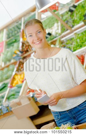 Lady in grocers with list