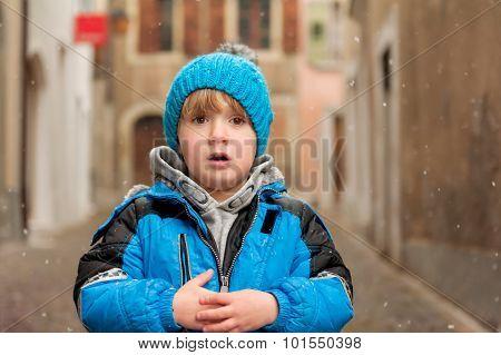 Outdoor portrait of a cute little boy in a city under snowfall, wearing warm blue jacket