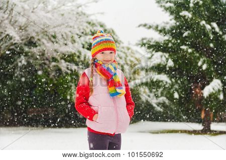 Winter portrait of a cute little girl under the snowfall, wearing red pullover