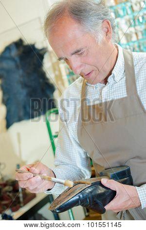 Cobbler painting sole of shoe