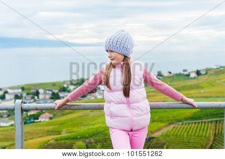 Kid girl standing between Lavaux vineyards, admire amazing view