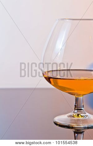 Snifter Of Brandy In Elegant Typical Cognac Glass On Light Background
